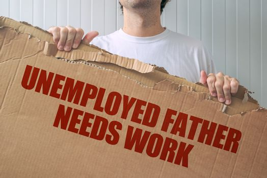 Unemployed father needs work, man holding banner