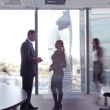 Business people talking in a conference room with city skyline