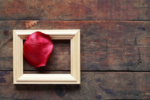 Romance concept. Red rose petal in picture frame on old wooden background