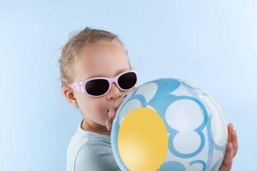 Summer. Adorable beautiful girl with ball and sunglasses against blue background. Summer background.