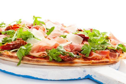 Culinary pizza with prosciutto, dry tomatoes and fresh herbs on wooden cutting board on white table.