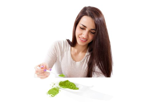 Detox. Beautiful girl with green ground powder on spoon isolated on white. Spirulina, chlorella and wheatgrass. Healthy lifestyle, detox.