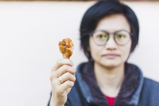 Hand holding grilled chicken wing, stock photo