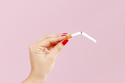 Last cigarette. Female hands with red fingernails breaking the last cigarette isolated on pink background. Quit smoking new year resolution.