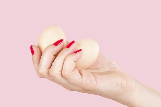 Female hand with red fingernails holding two eggs isolated on pink background. Feminism, emancipation, provocation and relationship problems.