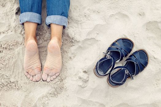 Relaxed sandy young woman feet and pair of shoes on the beach