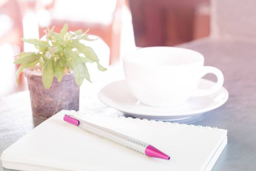 Notepad, pen and green plant on grey background