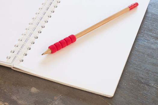 Blank notebook with pencil on grey background