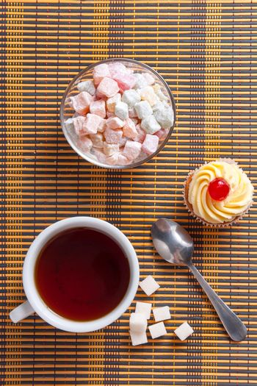 Tea, fresh cherry muffin, colorful delight and sugar