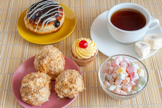 Tea, fresh cherry muffin, colorful delight, eclair and doughnut, various tasty sweet dessert