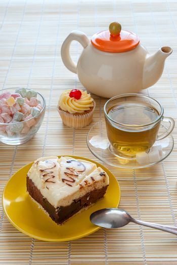 Green tea, fresh cherry muffin, cake on plate and colorful delight, various sweet dessert