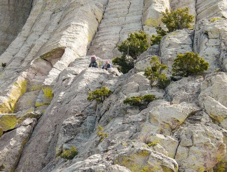 Devils Tower in Wyoming  Devils Tower, Wyoming, USA - May 11, 2008: Men climbing on the wall of famous mountain Devils Tower in the Black Hills (Wyoming).