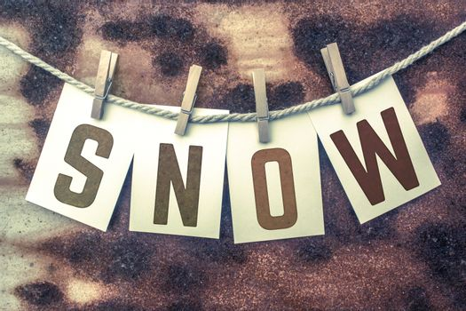 """The word """"SNOW"""" stamped on cards and pinned to an old piece of twine over a rusted metal background."""