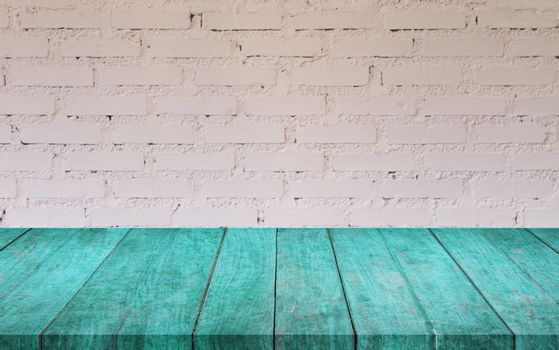 Blue wooden table top with white brick wall