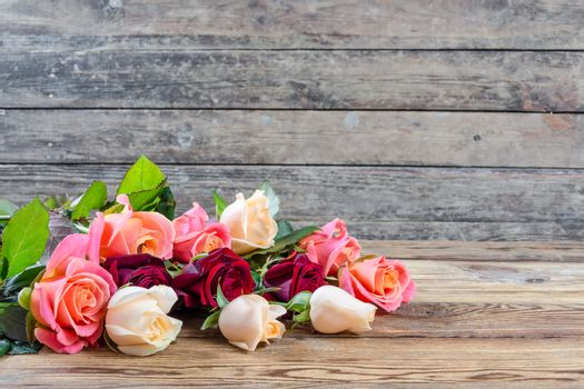Beautiful roses on old wooden table