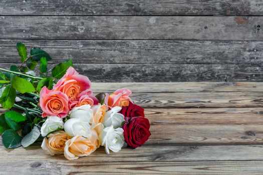 Beautiful bouquet of flowers roses on rustic wooden table