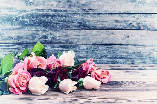 Vintage beautiful roses on old wooden table