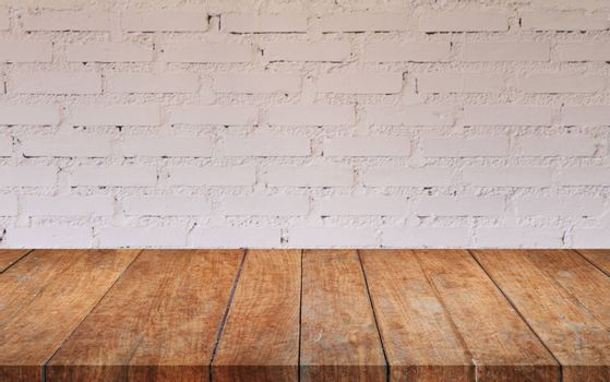 Brown wooden table top with white brick wall