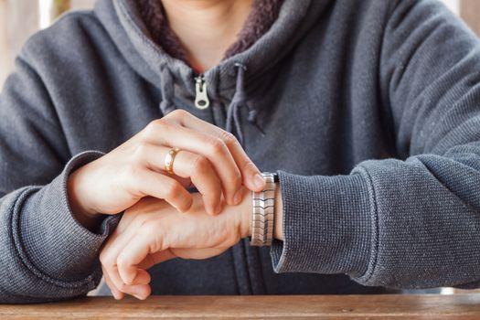 Woman checks the time on a wrist watch
