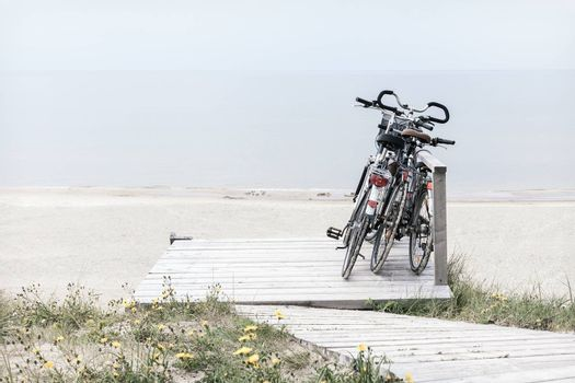 Three bicycles parked on wooden rest place by empty beach. Desaturated horizontally oriented picture