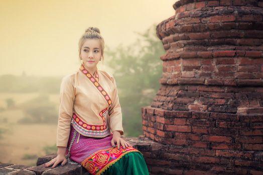 Beautiful girl in Myanmar traditional costume,  identity culture of Myanmar, Pagdodas of Bagan Background, Happy asian woman