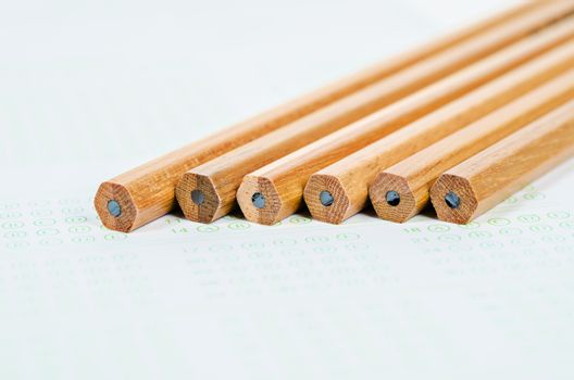Wooden pencils on answer sheets.