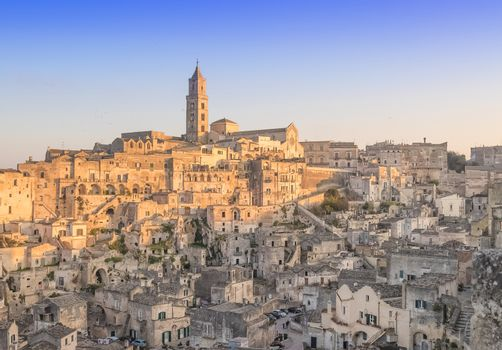 panoramic view of typical stones and church of Matera under begin sunset sky