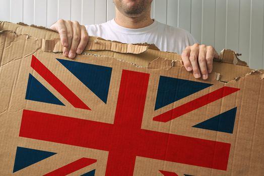 Man holding cardboard with United Kingdom flag printed