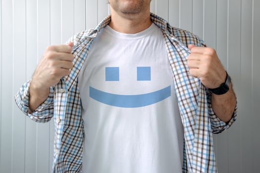 Man stretching shirt to reveal smiley emoticon