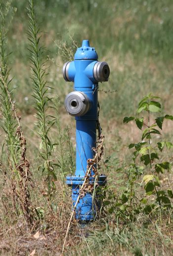 Blue aboveground hydrant in the field