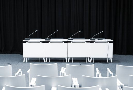 Monochrome picture of empty press conference room with seats, stand table and microphones