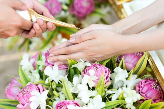 Thai wedding watering ceremony, hand of a bride receiving holy water from elders in thai culture wedding ceremony