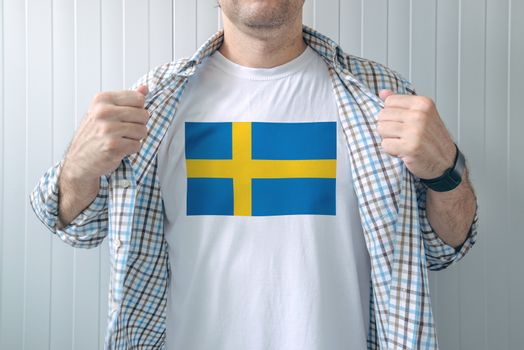 Man wearing white shirt with Sweden flag print
