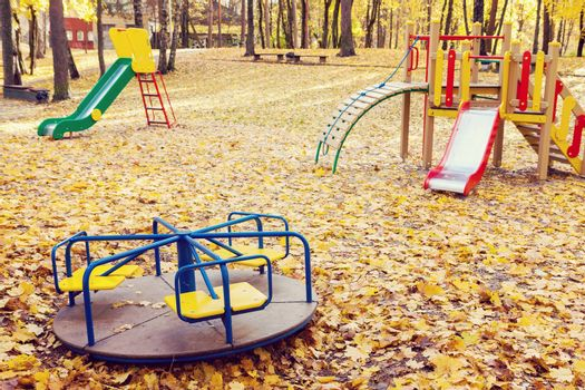Empty playground equipment in park full of yellow maple leaves at autumn