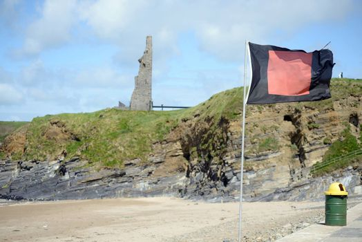 quicksilver flag flying beside surf school with ballybunion castle in background