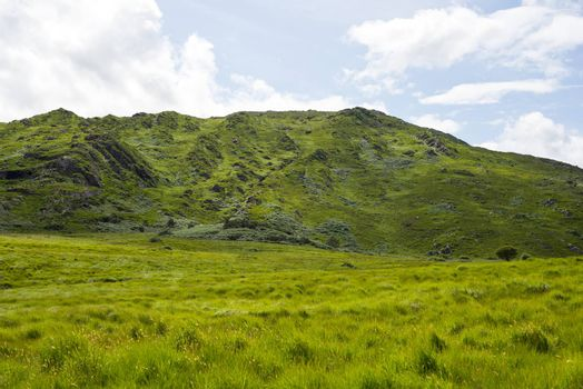 view from a beautiful hiking route the kerry way in ireland of rocky green mountains and fields