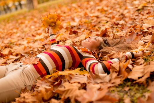 Beautiful young woman in sunny forest in autumn colors. She is lying on the ground covered with leaves and enjoying.