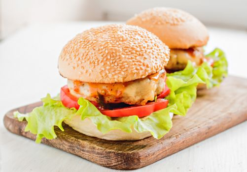 two hamburgers lay on a wooden board.