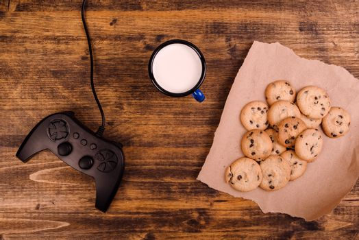 Gamepad and homemade chocolate chip cookies on rustic wooden tab