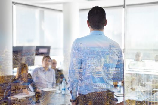Business man making a presentation at office. Business executive delivering a presentation to his colleagues during meeting or in-house business training. Rear view. Shalow depth of field.