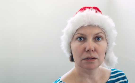 Surprised woman with Christmas Santa Claus hat in cheerful mood