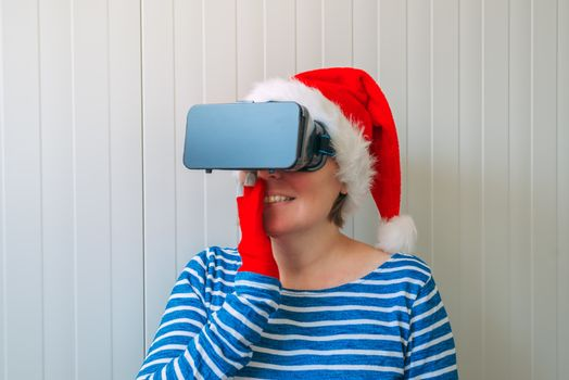 Woman with Christmas Santa Claus hat and VR headset