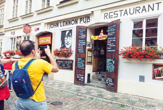 PRAGUE, CZECH REPUBLIC – JUNE 27, 2016: Tourists taking pictures of John Lennon pub entrance in Prague, Czech Republic