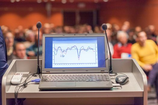 Computer and microphone on a podium desk at business event. Blured audience at the conference hall in background. Business and Entrepreneurship concept. Focus on computer.