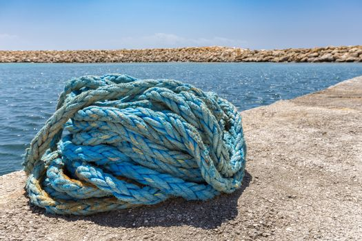 Coiled blue mooring rope at water in greek cave