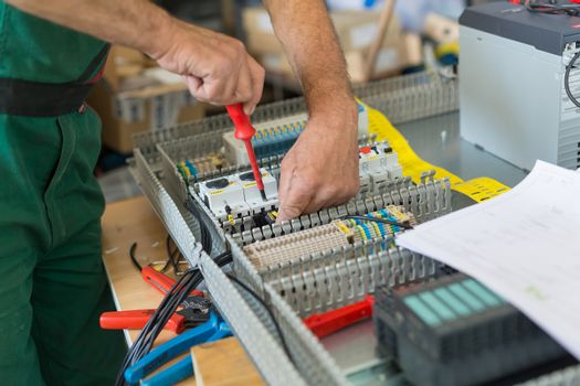 Electrician assembling industrial electric cabinet.