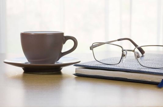 Glasses put on book and cofee cup on the desk by nature light from window