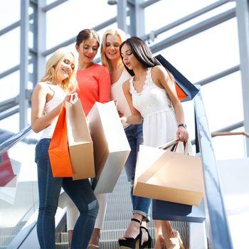 Young beautiful happy women on escalator of shopping mall