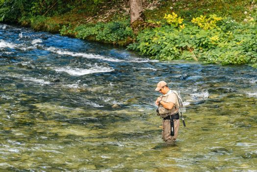 RIBCEV LAZ, SLOVENIA - AUGUST 22, 2016: Unidentifiable man fishing at Jezernica, second shortest river in Slovenia, flowing from Lake Bohinj for 100 meters to join Mostnica and form Sava Bohinjka.