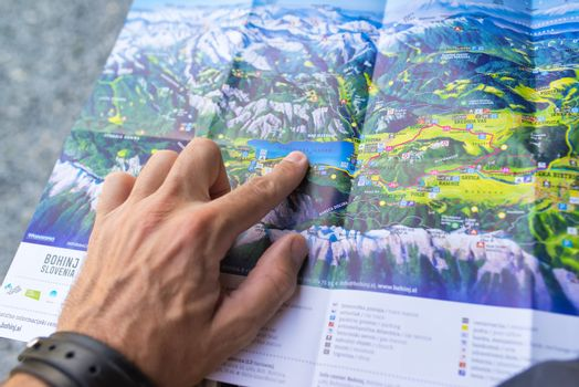 RIBCEV LAZ, SLOVENIA - AUGUST 25, 2016: Unidentifiable man looking at map of Bohinj lake area located in Slovenia national park Triglav.